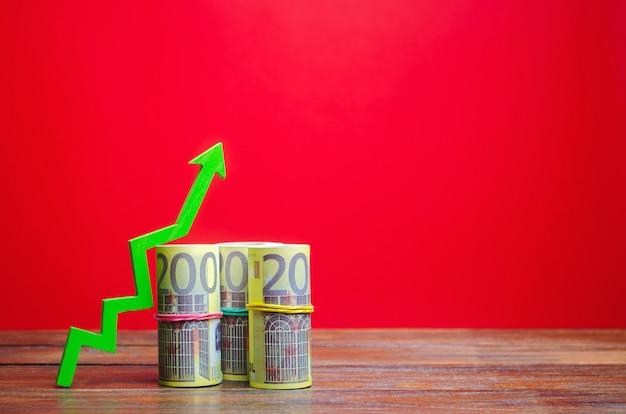 Rachunki w euro i zielona strzałka w górę. koncepcja udanego biznesu. zwiększ zyski i kapitał