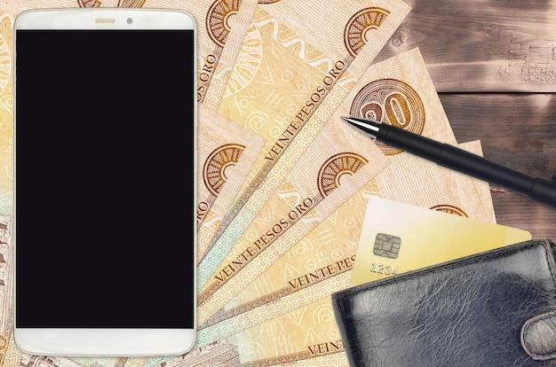 Rachunki w peso dominikańskim i smartfon z torebką i kartą kredytową