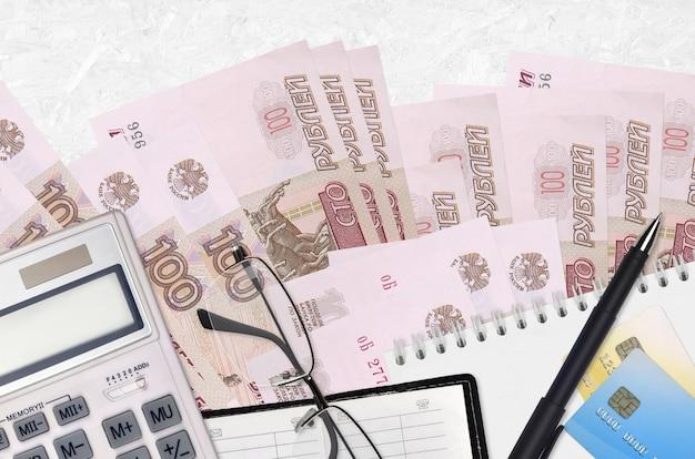 Rachunki w rublach rosyjskich i kalkulator z okularami i długopisem