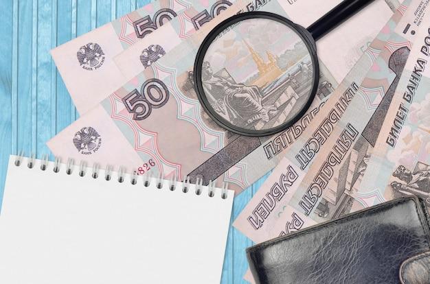 Rachunki w rublach rosyjskich i szkło powiększające z czarną torebką i notatnikiem