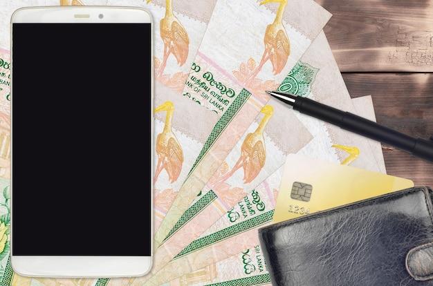 Rachunki w rupiach lankijskich i smartfon z torebką i kartą kredytową