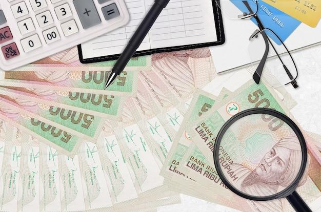 Rachunki w rupii indonezyjskiej i kalkulator z okularami i długopisem