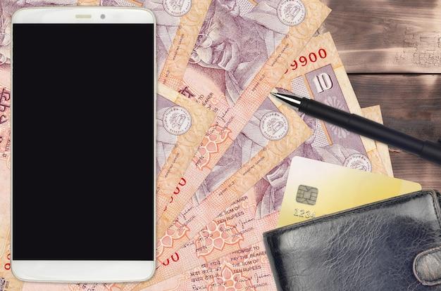 Rachunki za 10 rupii indyjskich oraz smartfon z torebką i kartą kredytową. e-płatności lub koncepcja e-commerce. zakupy online i biznes z wykorzystaniem urządzeń przenośnych