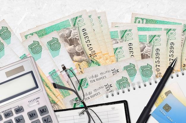 Rachunki za 10 rupii lankijskich i kalkulator z okularami i długopisem. koncepcja sezonu płatności podatku lub rozwiązania inwestycyjne. planowanie finansowe lub dokumenty księgowe