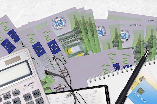 Rachunki za 100 euro i kalkulator z okularami i długopisem. koncepcja sezonu płatności podatku lub rozwiązania inwestycyjne. planowanie finansowe lub dokumenty księgowe
