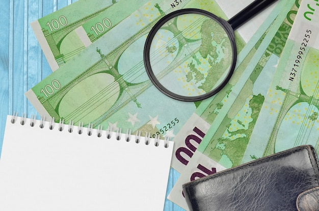 Rachunki za 100 euro i szkło powiększające, czarna torebka i notatnik