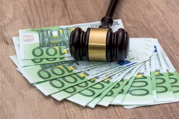 Rachunki za 100 euro z drewnianym młotkiem na biurku