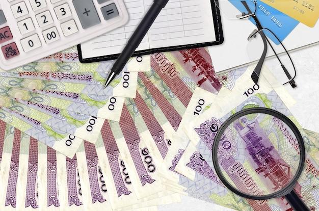 Rachunki za 100 riel kambodżańskich i kalkulator z okularami i długopisem. koncepcja sezonu płatności podatku lub rozwiązania inwestycyjne. poszukiwanie pracy z wysokimi zarobkami