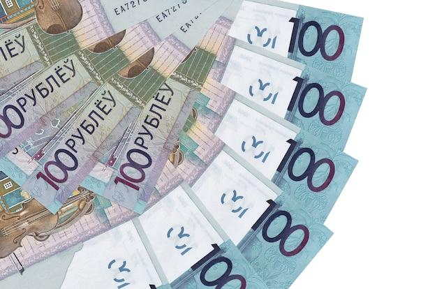 Rachunki za 100 rubli białoruskich leżą na białym tle ułożone w kształcie wachlarza z bliska. koncepcja transakcji finansowych