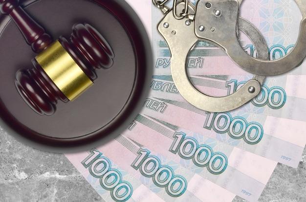 Rachunki za 1000 rubli rosyjskich i młotek sędziowski z policyjnymi kajdankami na ławce sądu. pojęcie procesu sądowego lub przekupstwa. unikanie podatków lub uchylanie się od opodatkowania