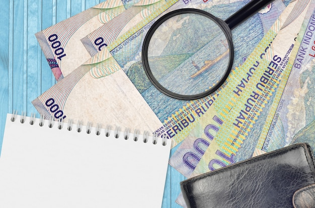 Rachunki za 1000 rupii indonezyjskich, lupa, czarna torebka i notes
