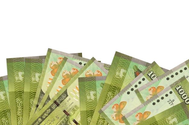 Rachunki za 1000 rupii lankijskich leżą w dolnej części ekranu na białej ścianie z miejsca na kopię.