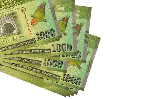 Rachunki za 1000 rupii lankijskich leżą w małej paczce lub paczce na białym tle. koncepcja biznesowa i wymiany walut