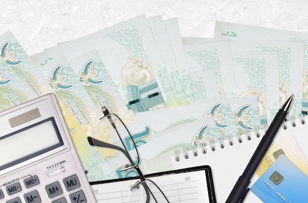 Rachunki za 20 bahtów tajskich i kalkulator z okularami i długopisem