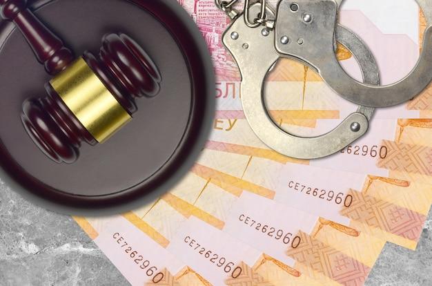 Rachunki za 20 rubli białoruskich i młotek sędziowski z policyjnymi kajdankami na biurku. pojęcie procesu sądowego lub przekupstwa. unikanie podatków lub uchylanie się od opodatkowania