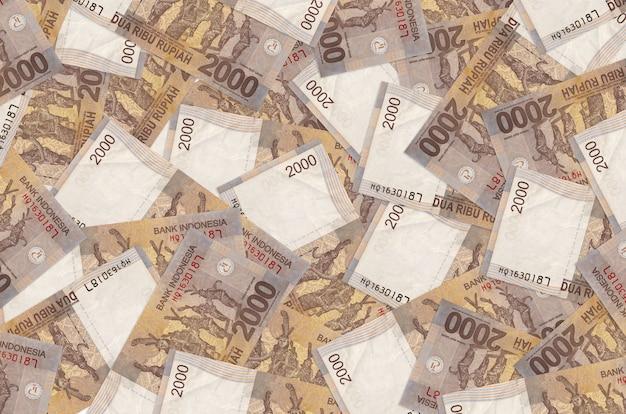 Rachunki za 2000 rupii indonezyjskiej leżą na stosie. . dużo pieniędzy