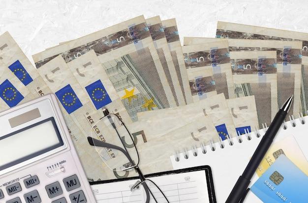 Rachunki za 5 euro i kalkulator z okularami i długopisem. koncepcja sezonu płatności podatku lub rozwiązania inwestycyjne. planowanie finansowe lub dokumenty księgowe