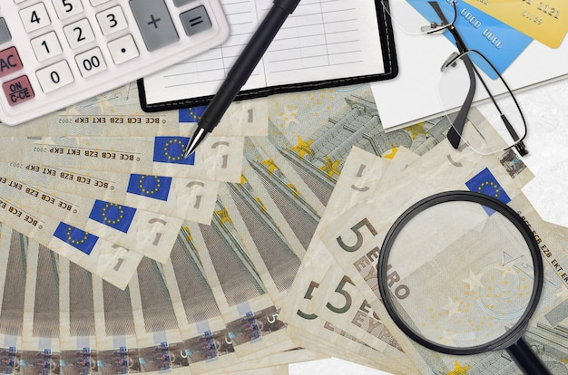 Rachunki za 5 euro i kalkulator z okularami i długopisem. koncepcja sezonu płatności podatku lub rozwiązania inwestycyjne. poszukiwanie pracy z wysokimi zarobkami