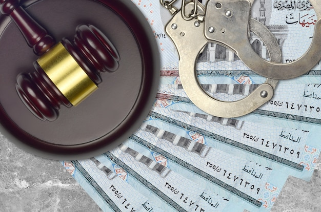 Rachunki za 5 funtów egipskich i młotek sędziowski z policyjnymi kajdankami na biurku. pojęcie procesu sądowego lub przekupstwa. unikanie podatków lub uchylanie się od opodatkowania