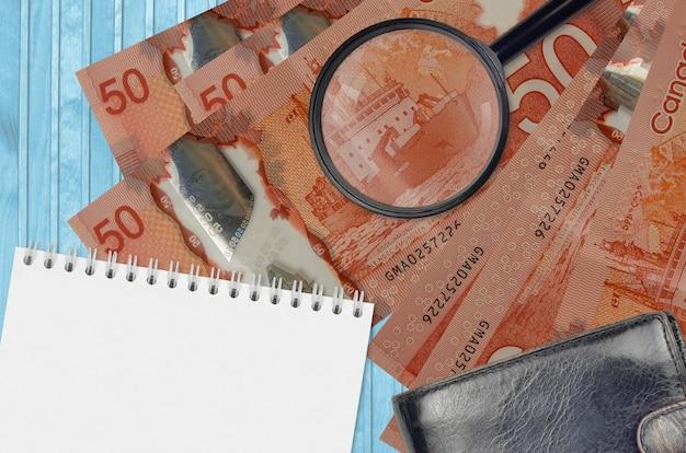 Rachunki za 50 dolarów kanadyjskich i szkło powiększające, czarna torebka i notatnik