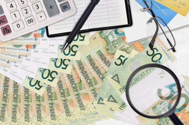 Rachunki za 50 rubli białoruskich i kalkulator z okularami i długopisem