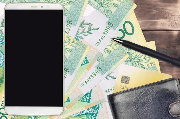 Rachunki za 50 rubli białoruskich i smartfon z torebką i kartą kredytową. e-płatności lub koncepcja e-commerce. zakupy online i biznes z wykorzystaniem urządzeń przenośnych