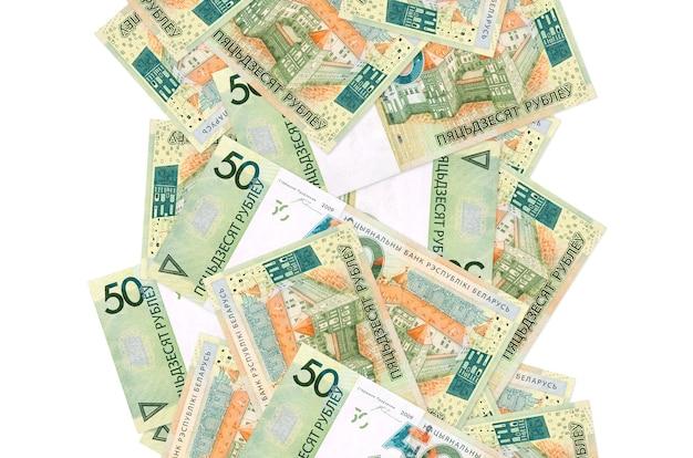 Rachunki za 50 rubli białoruskich lecą w dół na białym tle. wiele banknotów spada z białą przestrzenią na kopię po lewej i prawej stronie