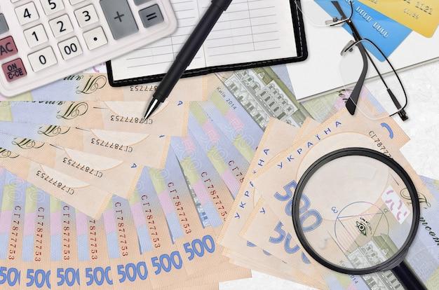 Rachunki za 500 hrywien ukraińskich i kalkulator z okularami i długopisem. koncepcja sezonu płatności podatku lub rozwiązania inwestycyjne. poszukiwanie pracy z wysokimi zarobkami