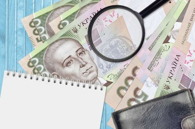 Rachunki za 500 hrywien ukraińskich i szkło powiększające, czarna torebka i notatnik