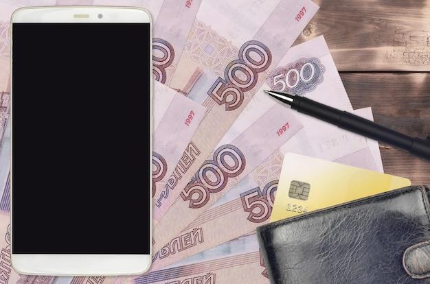 Rachunki za 500 rubli rosyjskich, smartfon z torebką i kartą kredytową. e-płatności lub koncepcja e-commerce. zakupy online i biznes za pomocą urządzeń przenośnych