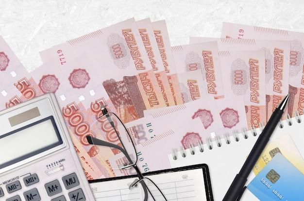 Rachunki za 5000 rubli rosyjskich i kalkulator z okularami i długopisem. koncepcja płatności podatku lub rozwiązania inwestycyjne. planowanie finansowe lub dokumenty księgowe