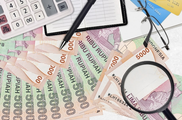 Rachunki za 5000 rupii indonezyjskich oraz kalkulator z okularami i długopisem