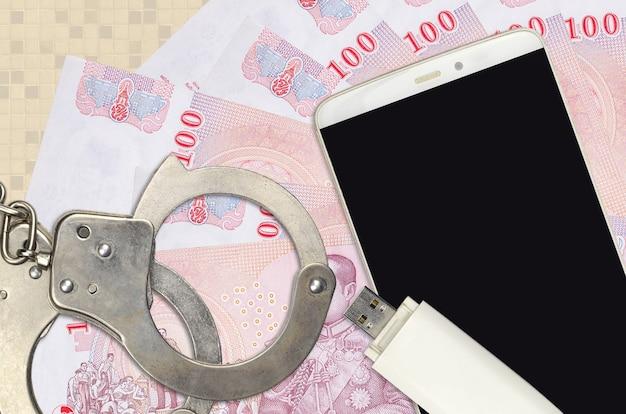 Rachunki za baht tajski i smartfon z policyjnymi kajdankami