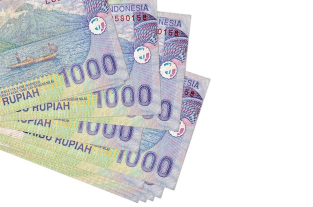 Rachunki za rupię indonezyjską leżą w małej paczce lub paczce na białym tle