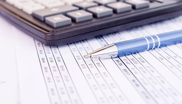 Rachunkowość finansowa. długopis i kalkulator na bilansach
