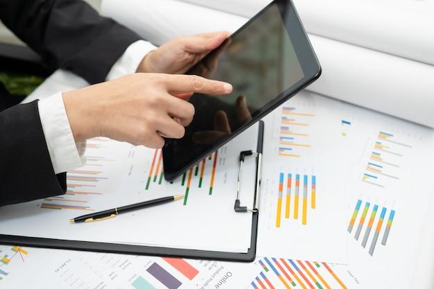 Rachunkowość tablet prasowy z wykresem dla pracującego projektu w biurze.