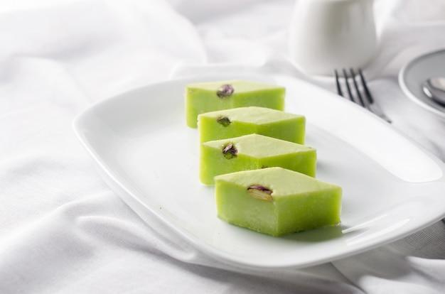Racjonalna turecka rozkosz z kawą na śniadanie. arabski deser pistacje chałwa i rahat lokum w białym talerzu na stole z miejscem na tekst. turecka rozkosz.