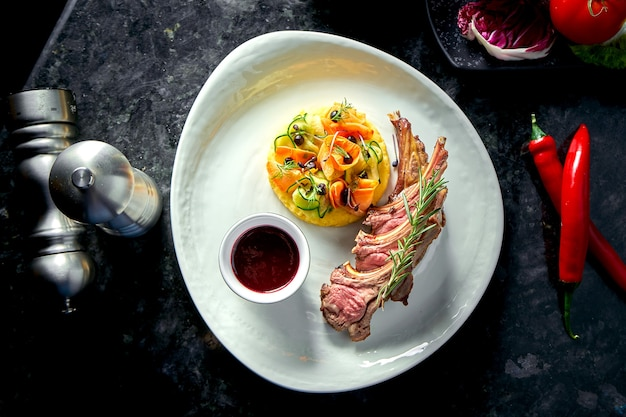Rack jagnięciny średnio wysmażony z puree warzywnym i sosem jagodowym, podawany na białym talerzu. stół z ciemnego marmuru. mięso, jedzenie w restauracji