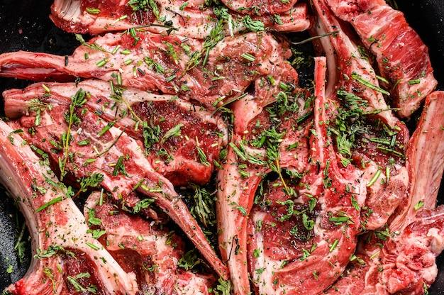 Rack jagnięcy marynowany tymiankiem i miętą, surowe mięso z kością. organiczne mięso jagnięce. czarne tło. widok z góry