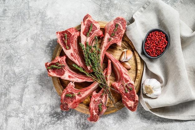 Rack jagnięcy, surowe mięso z kością, kotlety z solą, pieprz. szare tło. widok z góry