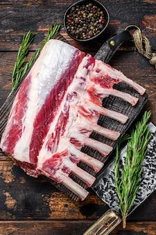 Rack surowego mięsa jagnięcego z kością na deska do krojenia. ciemne tło drewniane. widok z góry.
