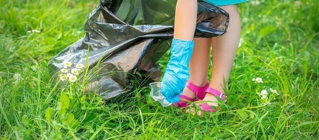 Rączka dziecka czyści park z plastikowych przyborów na trawie w parku