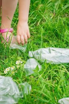 Rączka dziecka czyści zieloną trawę z plastikowych śmieci w parku