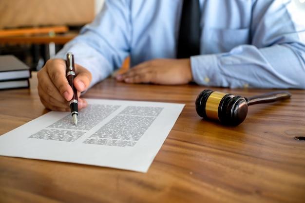 Radca prawny przedstawia klientowi podpisaną umowę z młotkiem i prawem
