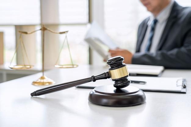 Radca w garniturze lub prawnik pracujący nad dokumentami. sędzia młotek i szalę sprawiedliwości.