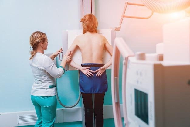 Radiolog i pacjent w pokoju rtg. klasyczny sufitowy system rentgenowski.