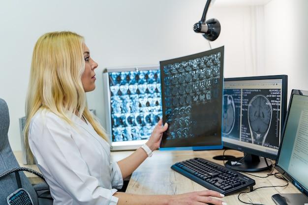 Radiolog kobieta trzymając kliszy rentgenowskiej w pobliżu komputera. biuro tło. nowoczesny sprzęt.