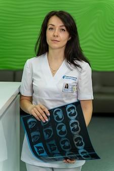 Radiolog kobieta z rtg w ręce. biuro tło. radiolog w pracy.