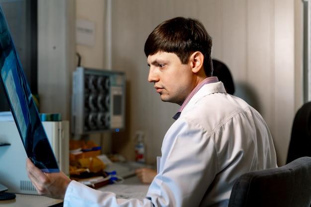 Radiolog w pracy. czytanie mri w pobliżu komputera. problemy medyczne. koncepcja neurochirurgii.