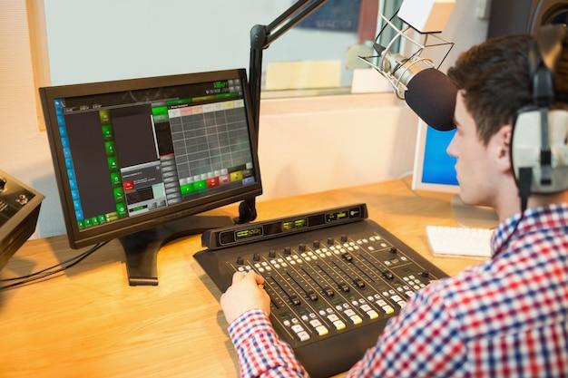 Radioodtwarzacz obsługujący mikser dźwięku podczas patrzenia w monitor